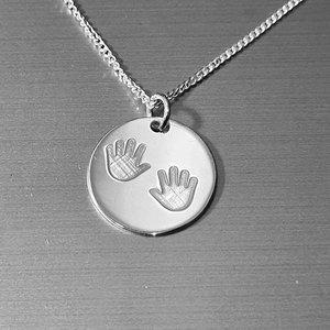 zilveren hanger met kinderhandjes